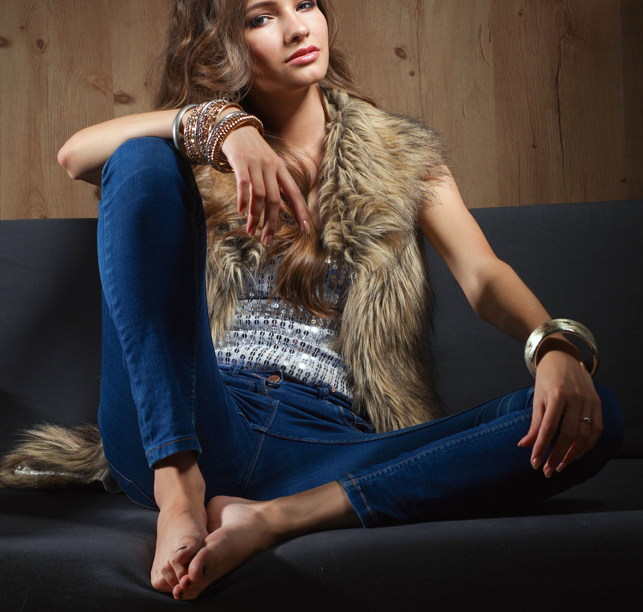 61832418 - portrait of a elegant woman sitting on a black sofa wearing a blue jeans and fur vest