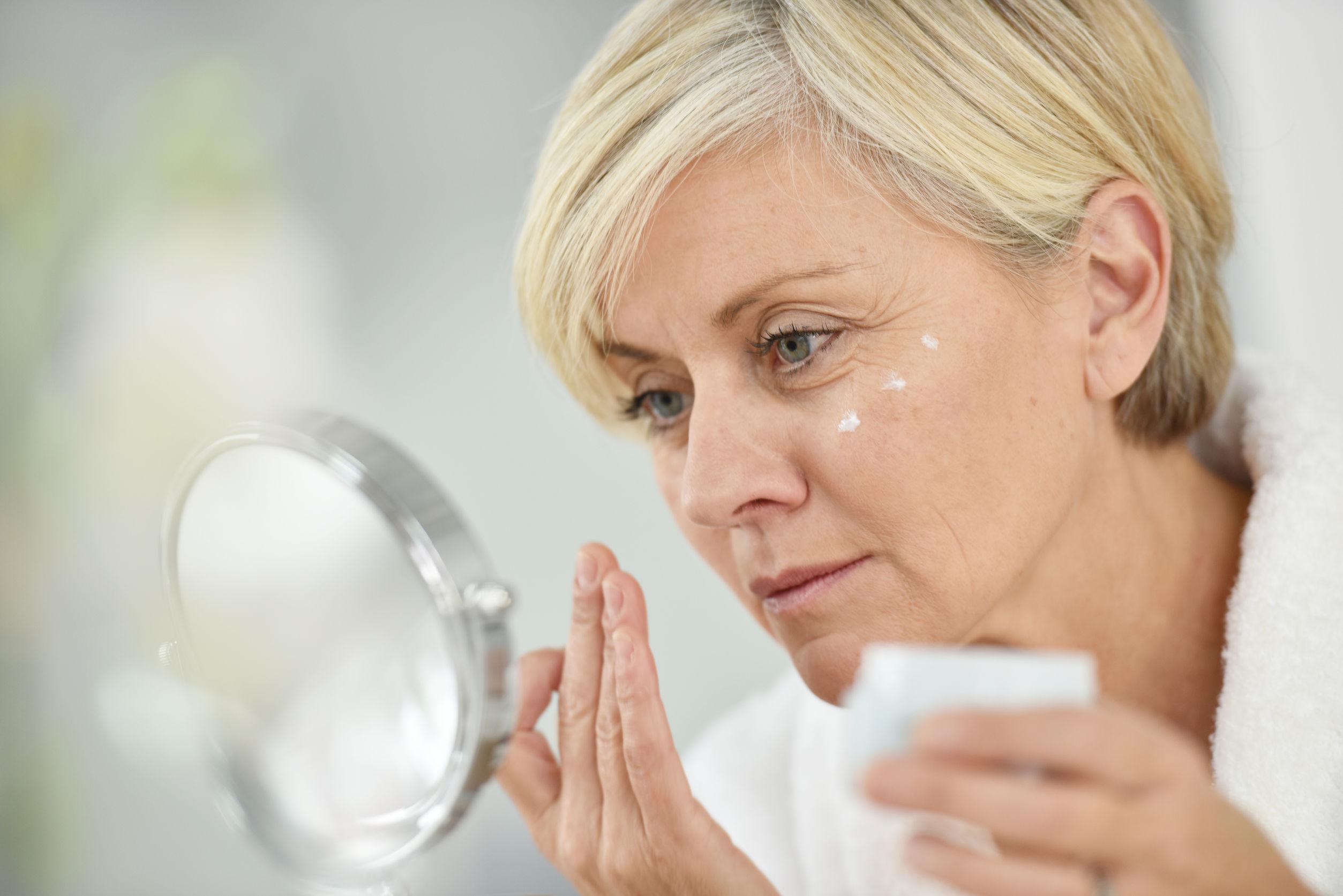 48551939 - senior woman in bathroom applying anti-aging lotion