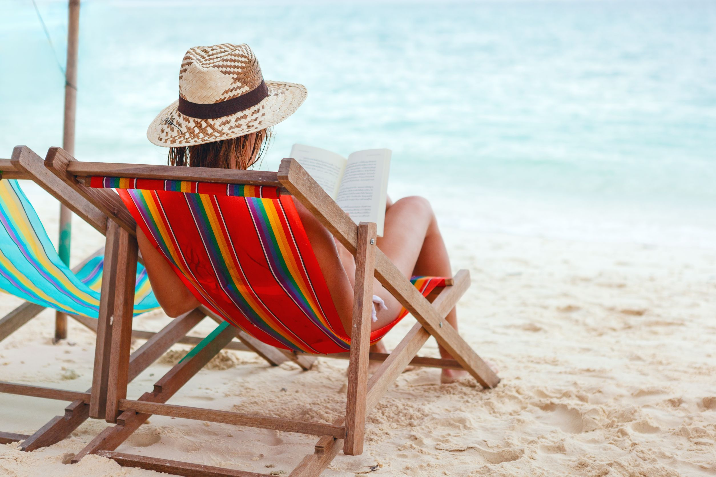 17444511 - young beautiful woman sitting on beach reading a book