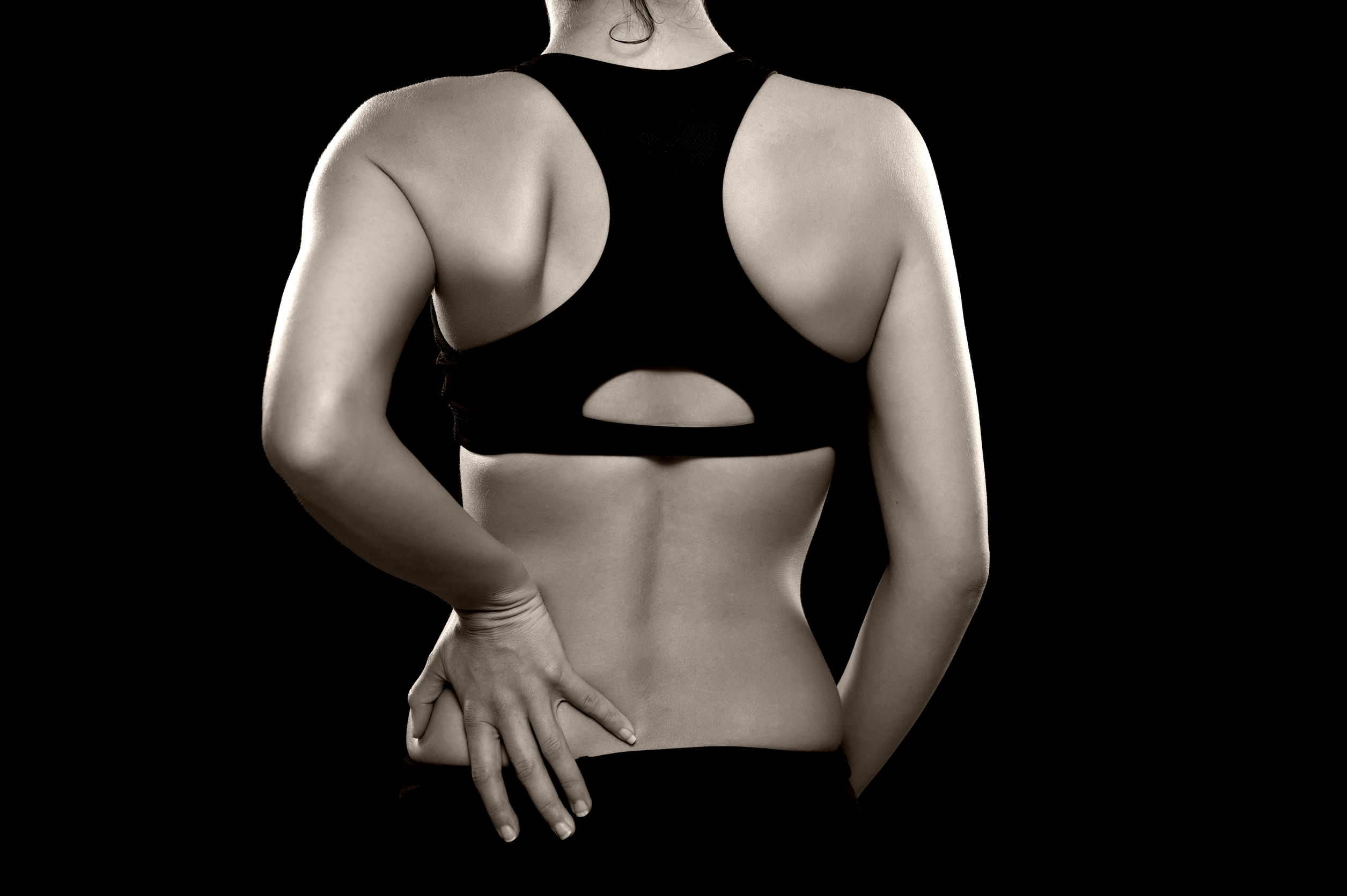20494423 - a black and white photo of an athletic woman holding her lower back as if experiencing pain