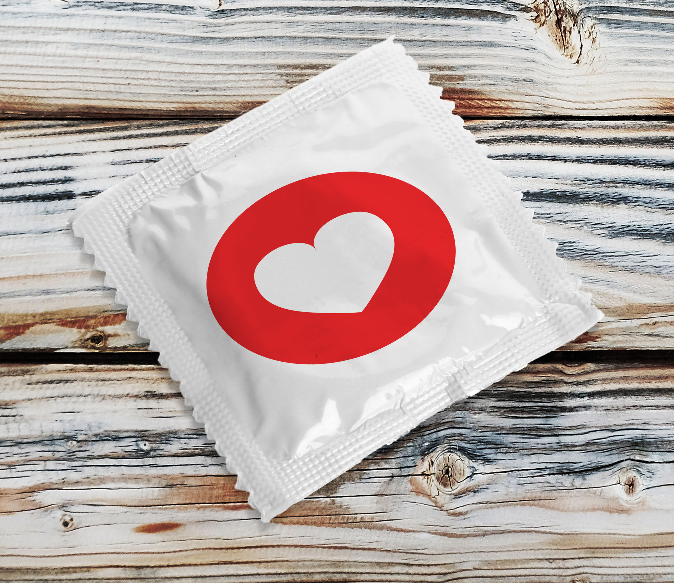49661866 - condom with heart on wooden table