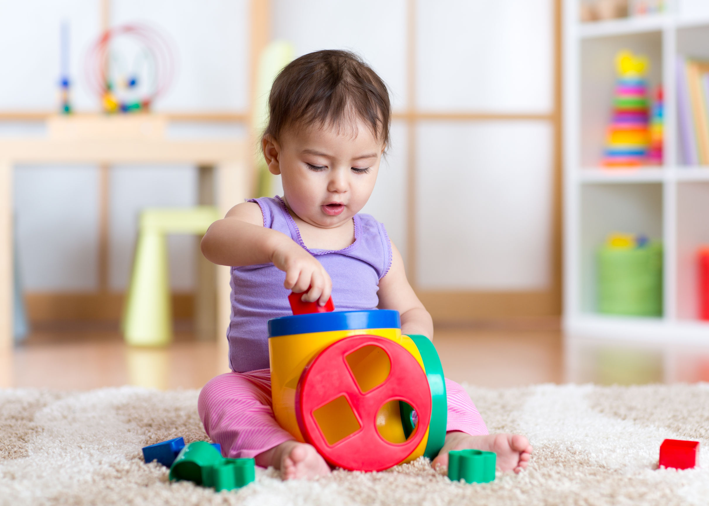 54307076 - cute toddler girl playing indoors with sorter toy sitting on soft carpet