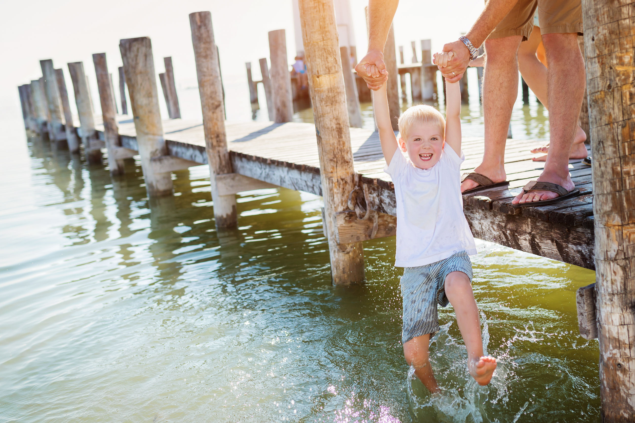 51994586 - father standing on the pier holding his son above water on sunny summer day