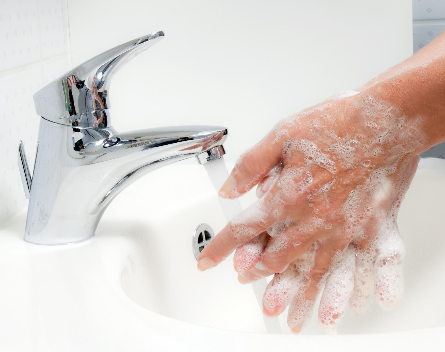 Frau wäscht sich mit fließendem wasser und Seife die Hände. Schutz vor Infektion der neuen Grippe.