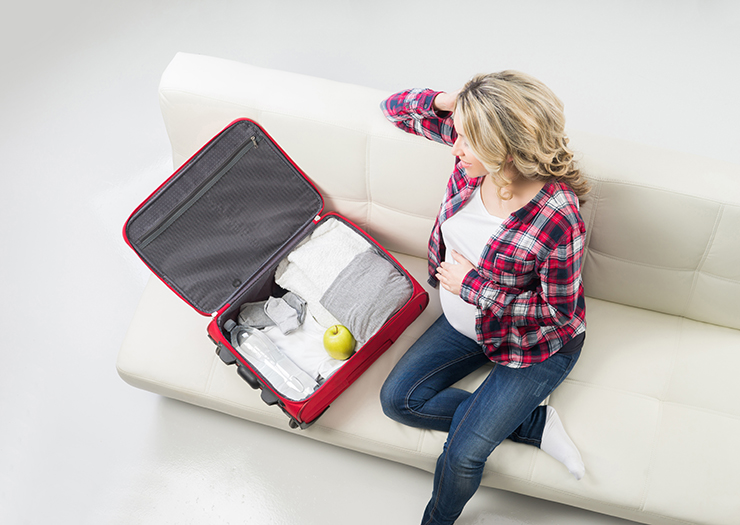 Young pregnant woman packing on a sofa