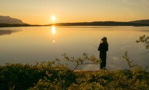 2018/07/lagom-szwedzki-sposob-na-szczesliwe-zycie-midnightsun-in-the-arctic-a-girl-is-fishing-in-front-of-the-great-picture-id1219127615.jpg
