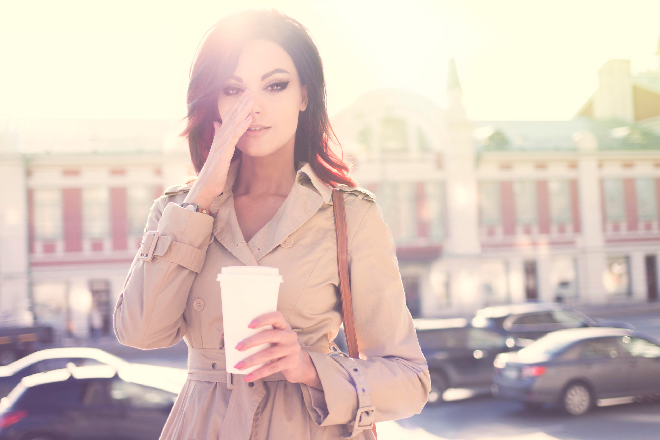 41237201 - beautiful young woman in a modern trench coat, holding a disposable takeaway cup and standing against urban city background.