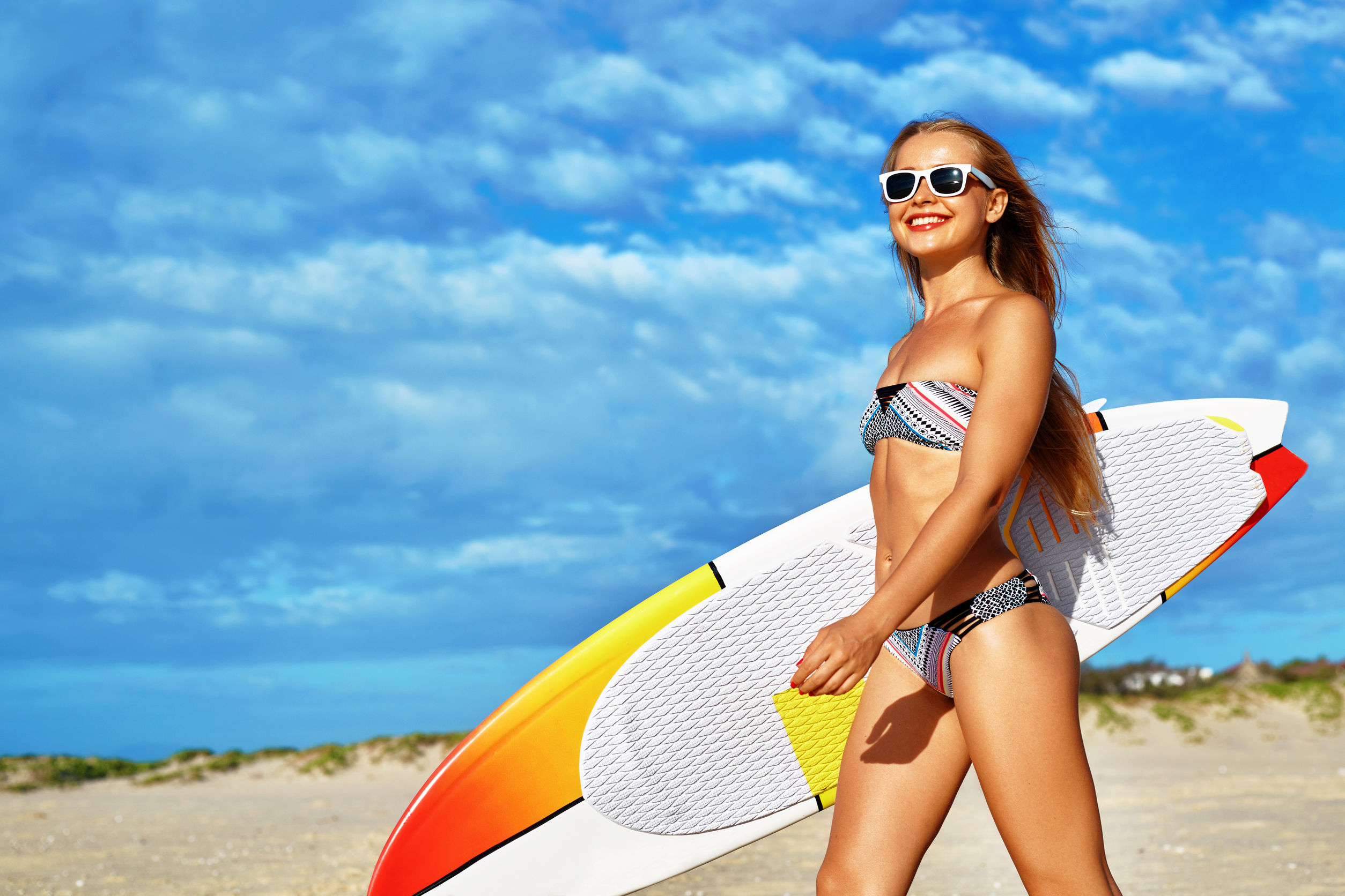 54194693 - healthy active lifestyle. surfing. water sports. beautiful athletic surfer woman with sexy fit body in bikini with surf board walking on sea beach. summer vacation. extreme sport. summertime fun hobby