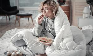2015/02/zajadanie-emocji-zaburzone-wzorce-odzywiania-sad-and-lonely-woman-eating-burger-and-french-fries-in-the-bed-picture-id1136220868.jpg