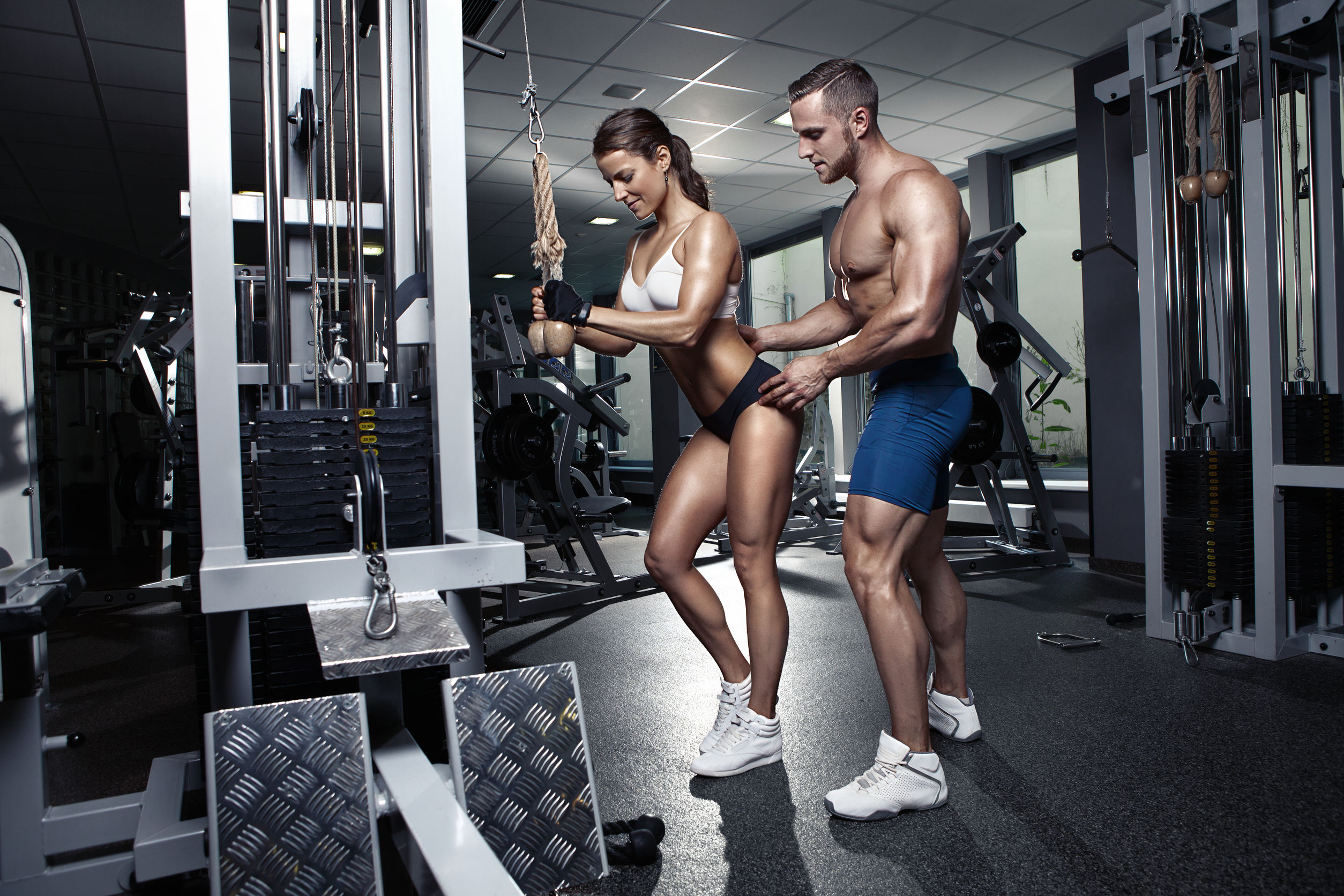 41521337 - beautiful young sporty sexy couple doing triceps workout in gym