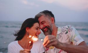 2015/10/couple-celebrating-with-sparklers-at-the-beach-picture-id1124335767.jpg