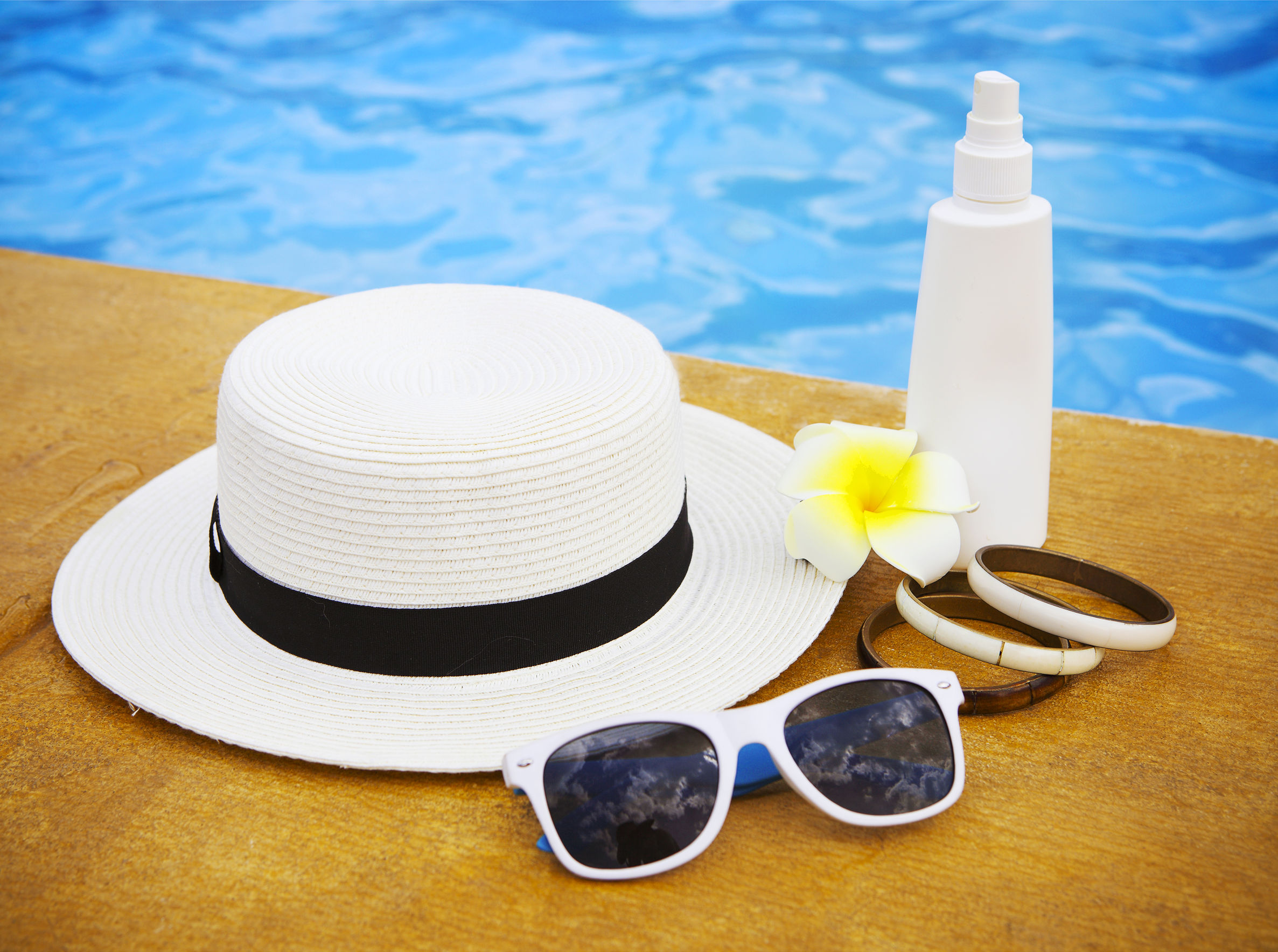 57290419 - suncream, sunglasses, hat, bracelet near the swimming pool. vacation concept