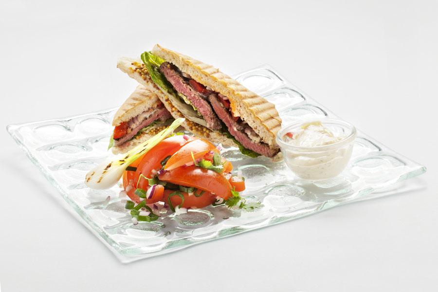 Kanapka z ciabaty z wołowiną z rozpuszczonym serem niebieskim, z sałatką z pomidorów, z kolendrą i wiosenną cebulką