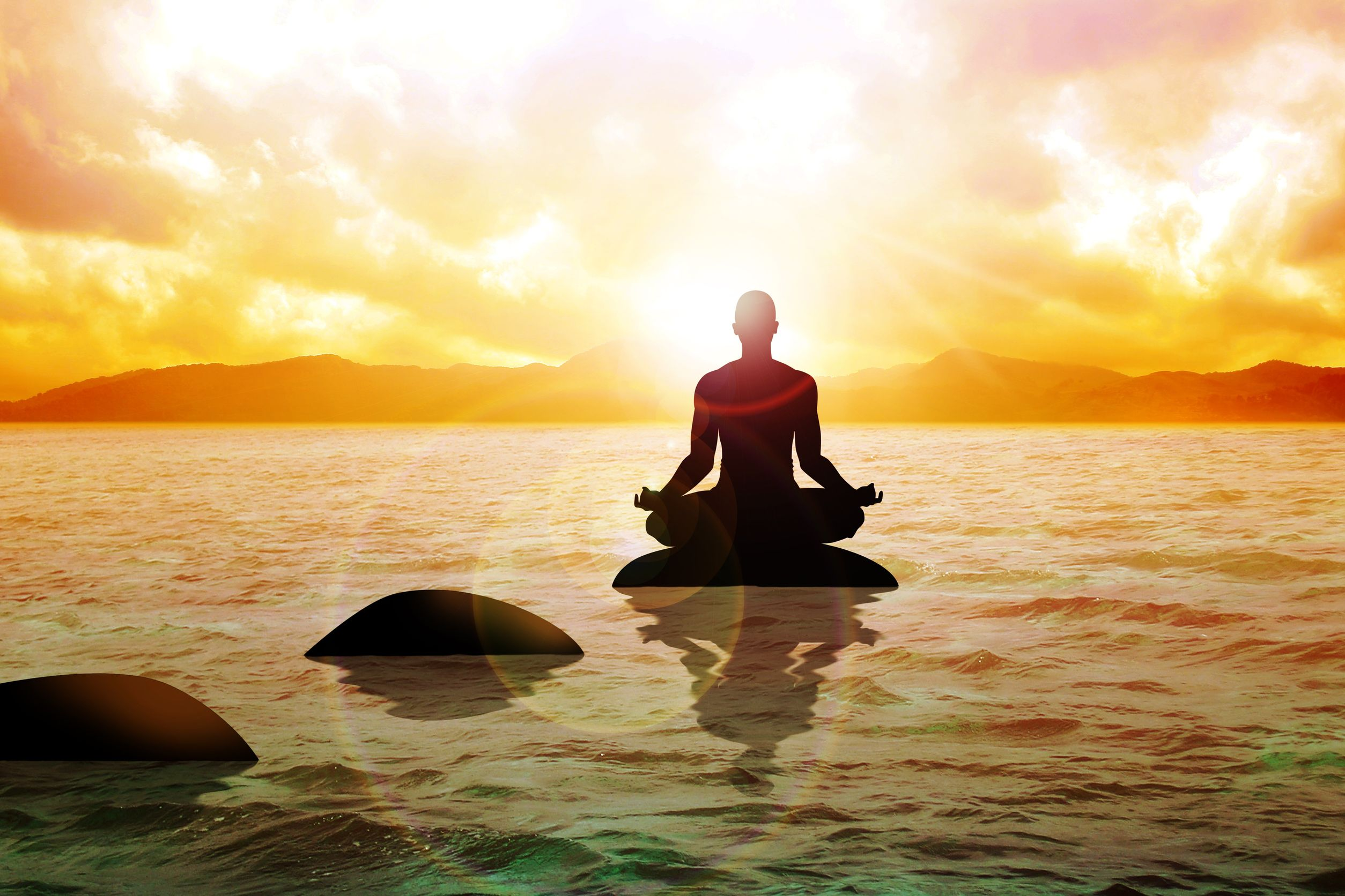 15941951 - silhouette of a man figure meditating on calm water during sunrise