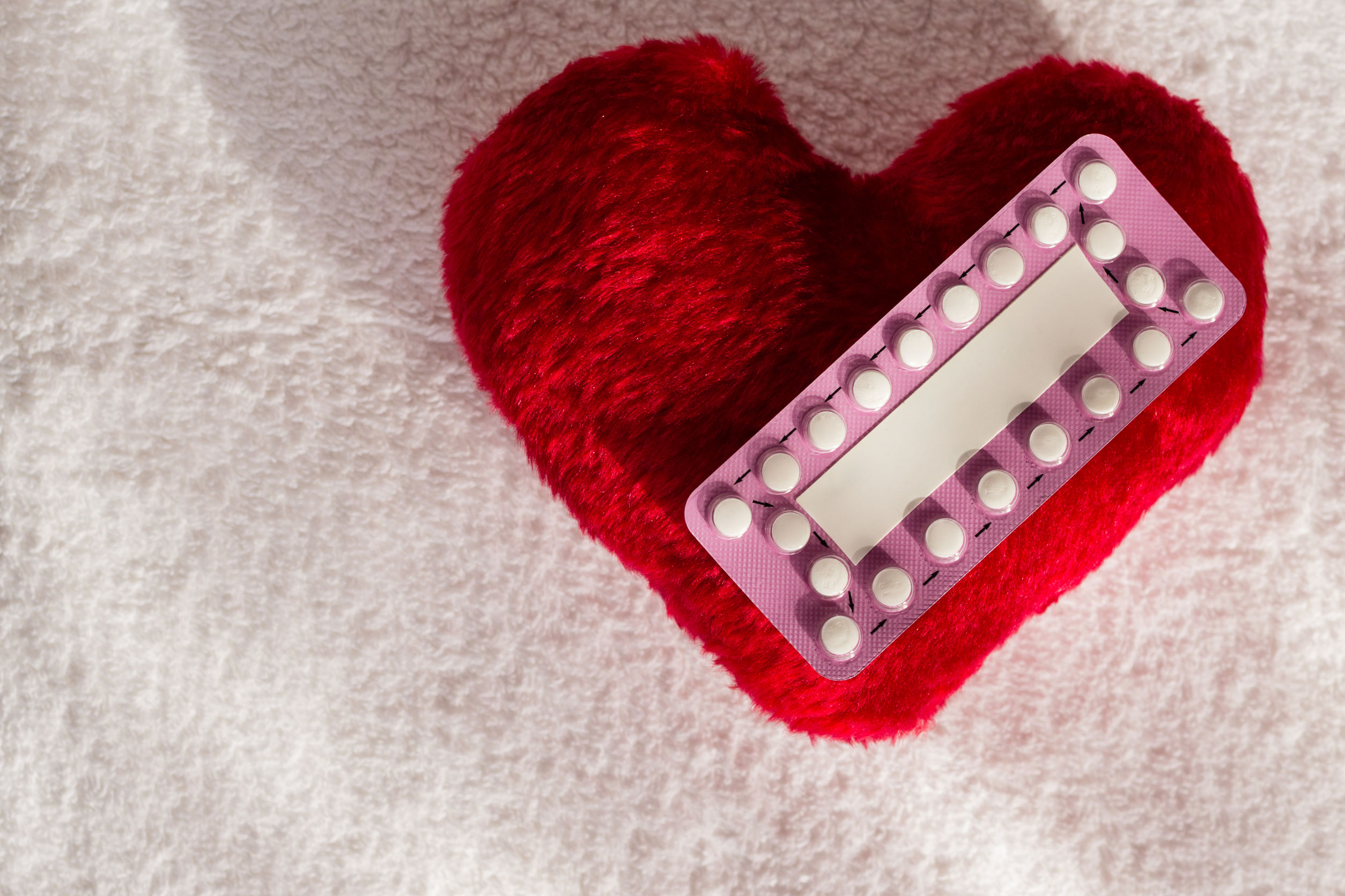 60676423 - medicine contraception love and birth control. oral contraceptive pills on red heart shaped little pillow