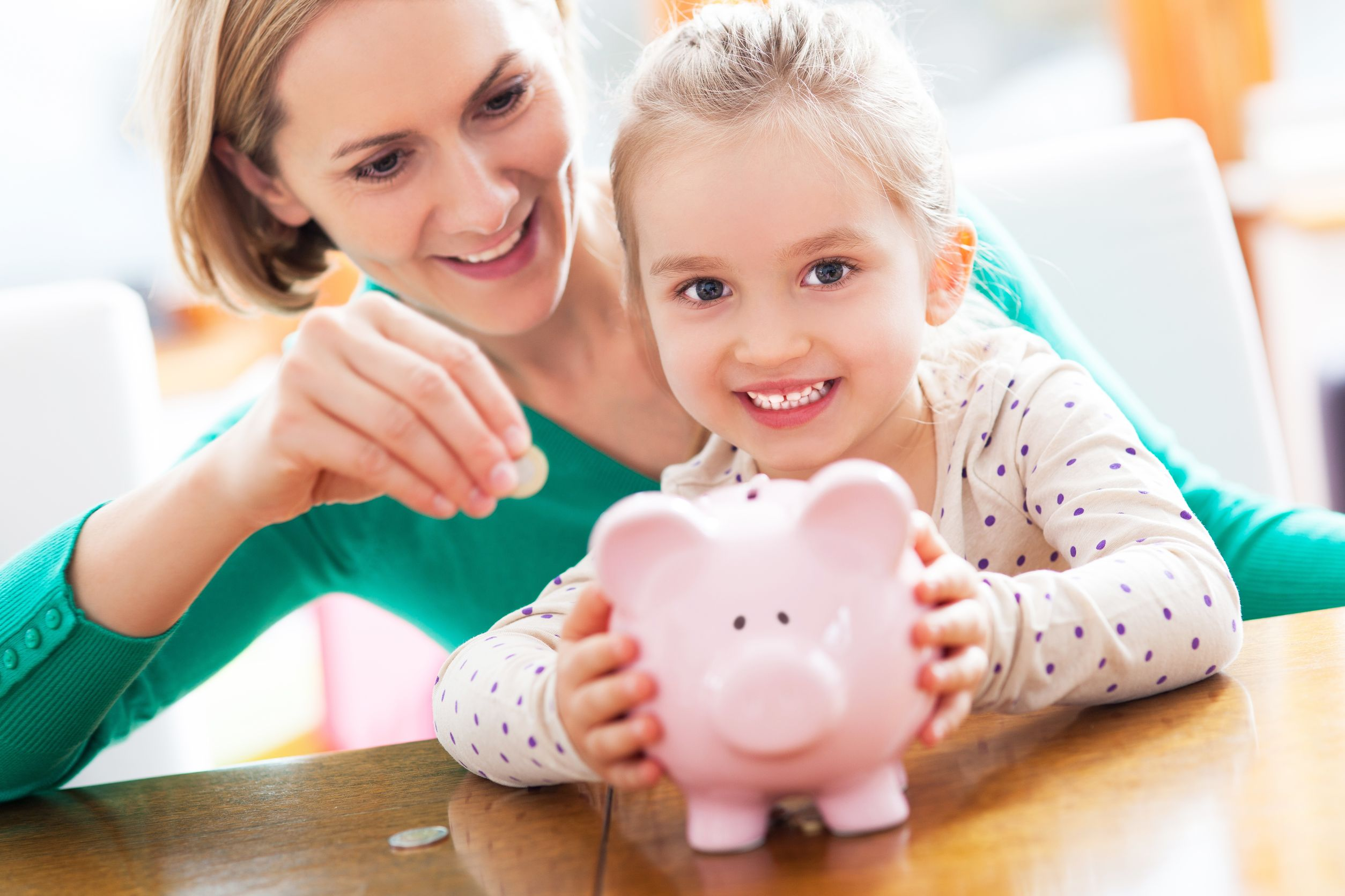 16193879 - mother and daughter putting coins into piggy bank