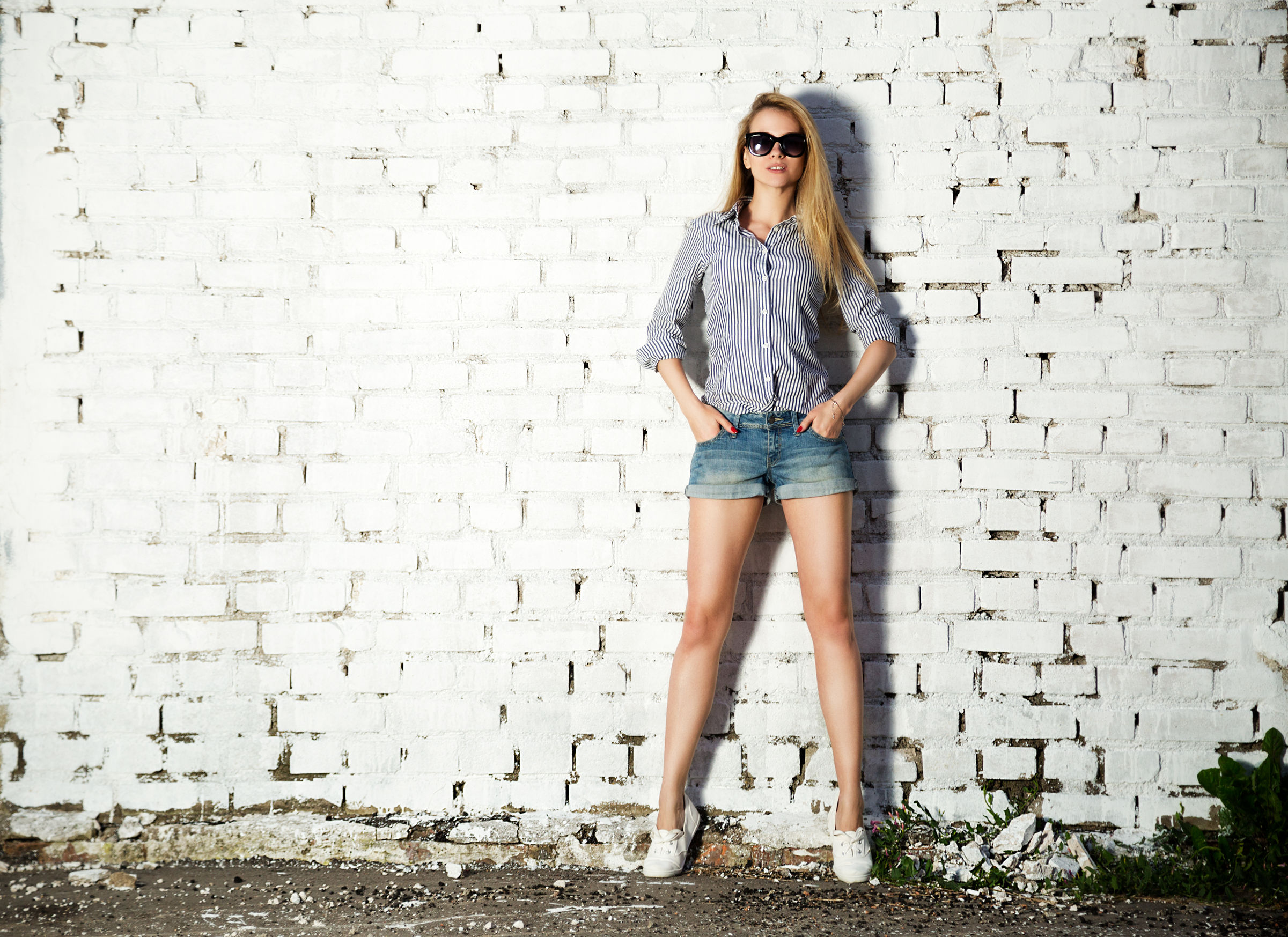 38110443 - full length portrait of trendy hipster girl with hands in pockets on white brick wall background. trendy urban fashion concept. copy space.