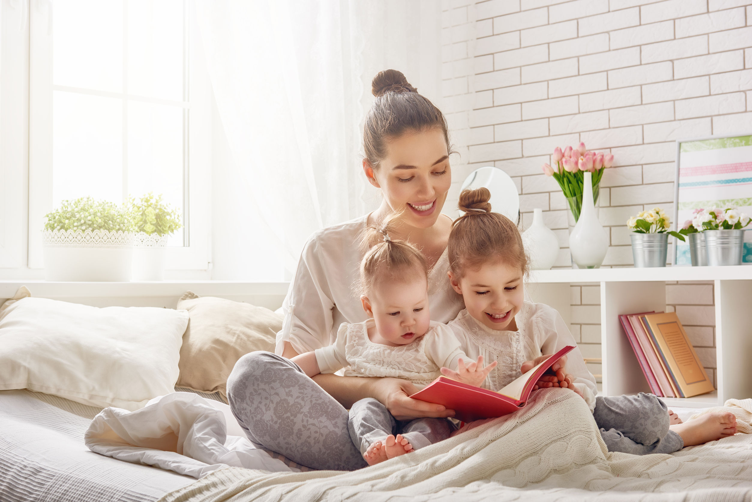 54018592 - happy loving family. pretty young mother reading a book to her daughters