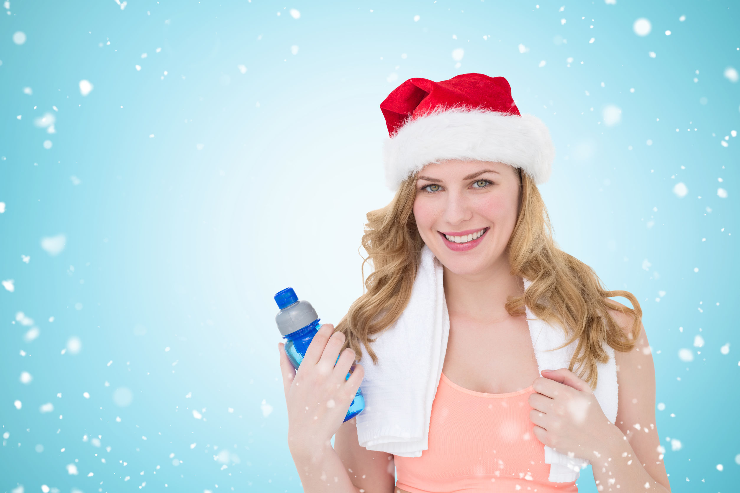 66779333 - festive fit blonde holding bottle of water against christmas snow falling