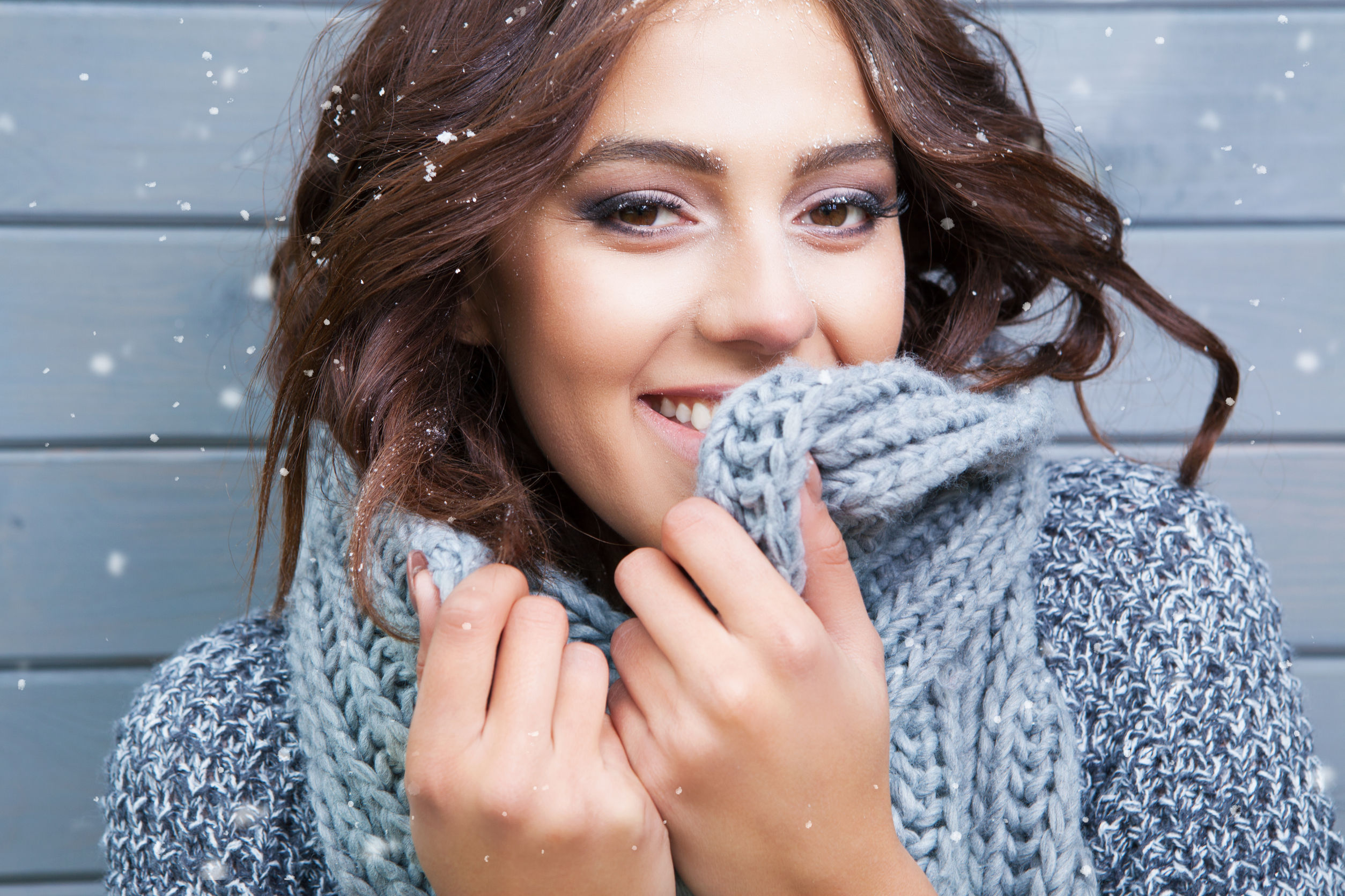48119311 - beautiful natural looking young smiling brunette woman, wearing knitted scarf, covered with snow flakes. snowing winter beauty concept.