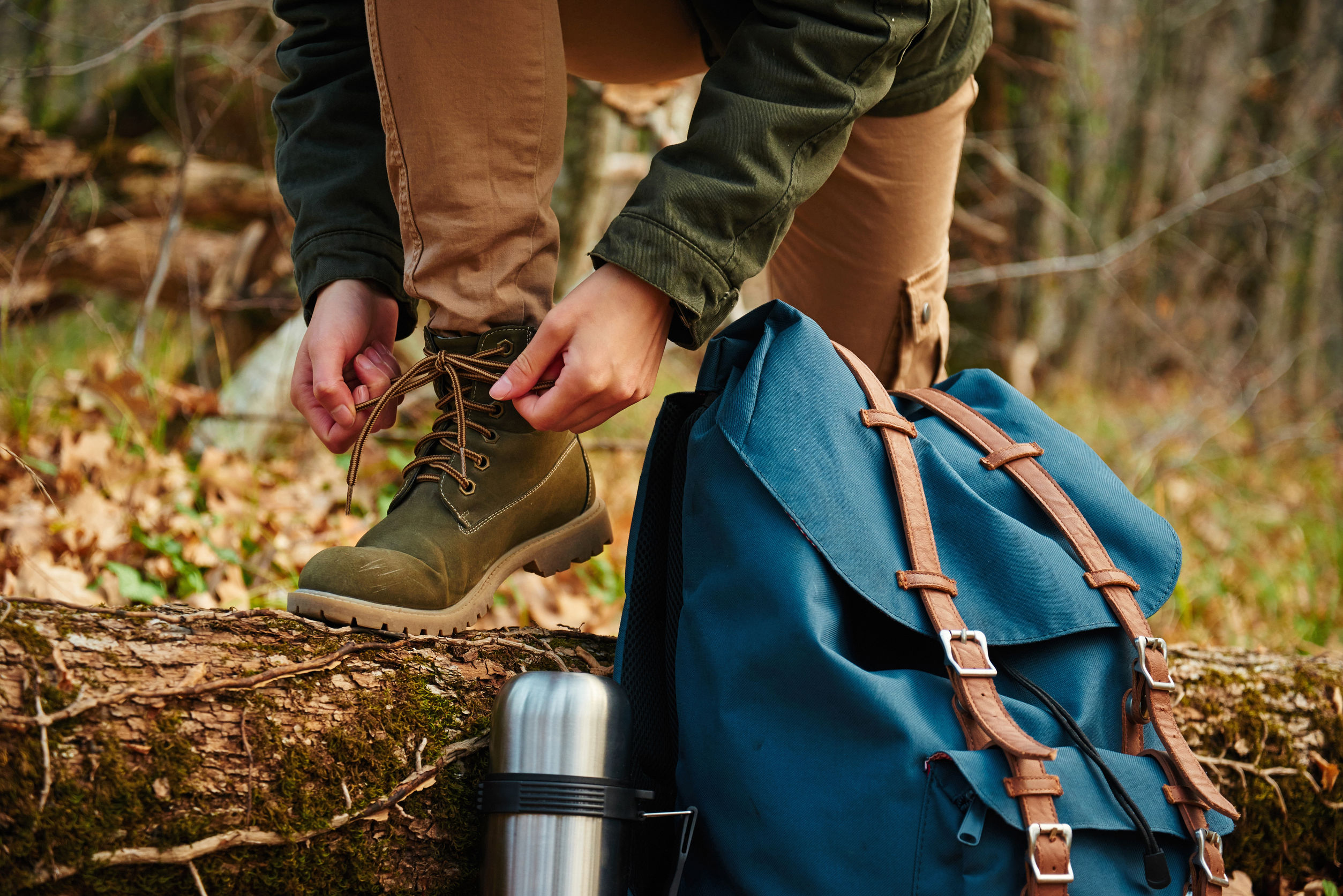 33853055 - female hiker tying shoelaces outdoors in autumn forest, near thermos and backpack. view of legs. hiking and leisure theme