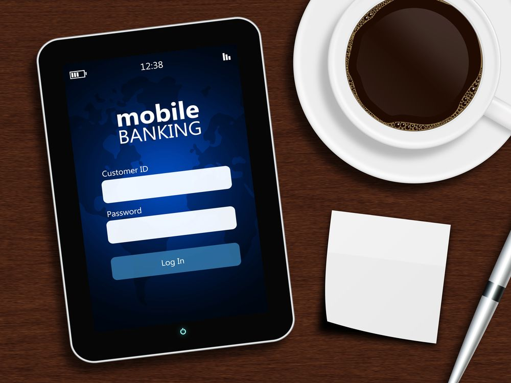 tablet with mobile banking login page, cup of coffee, pen and white note lying on wooden desk