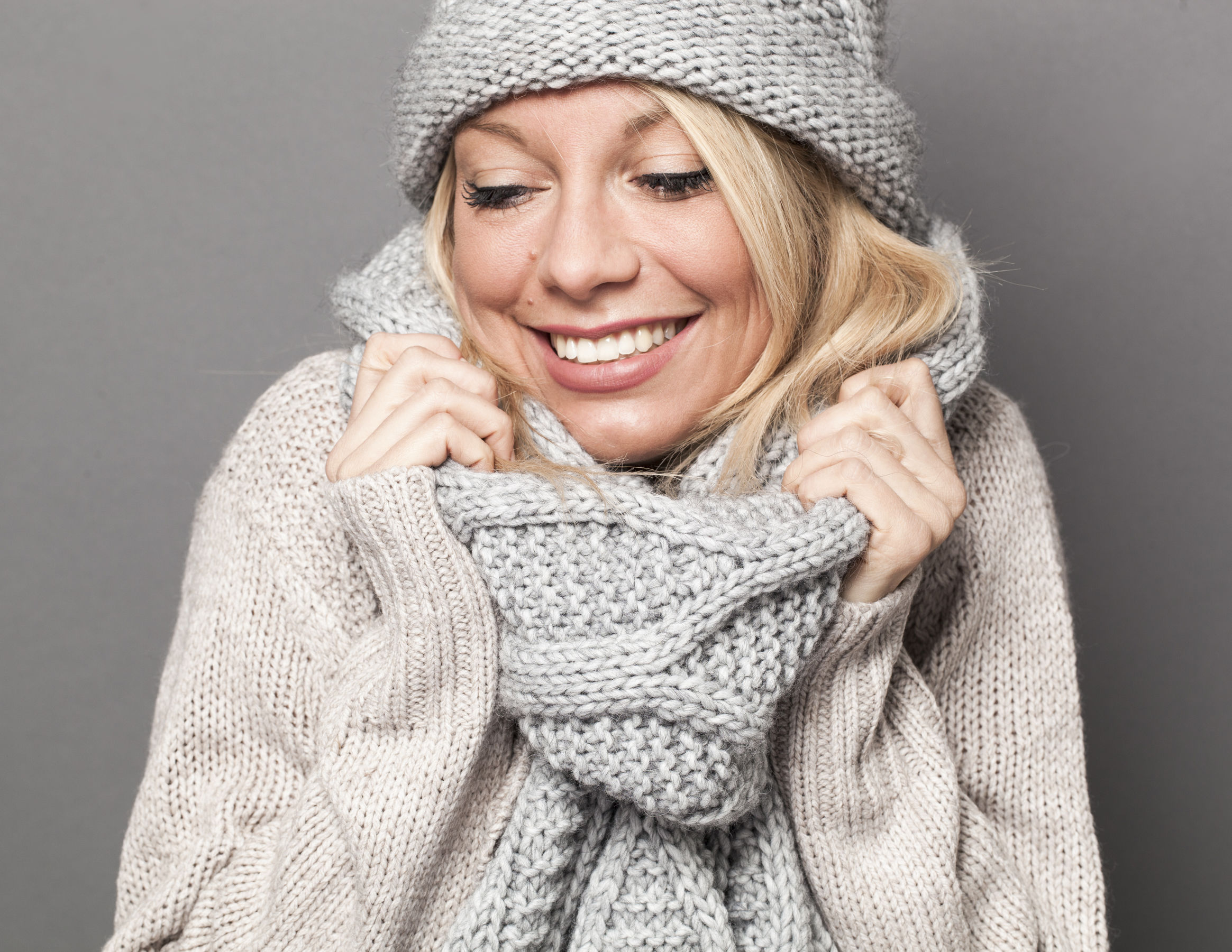 47014101 - trendy warm winter - gorgeous young blond woman wrapping up herself in gray wool winter hat and scarf smiling for softness and cozy fashion