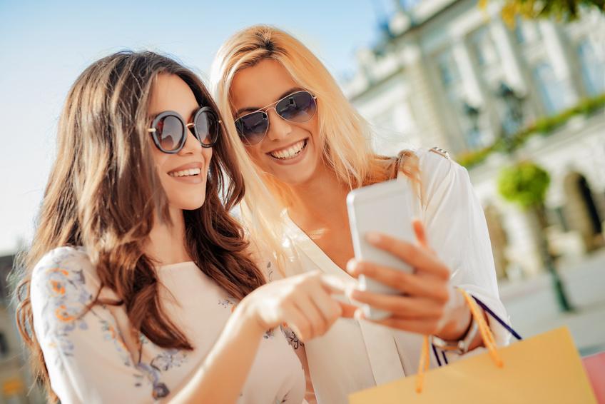 Beautiful smiling girls making selfie after good shopping