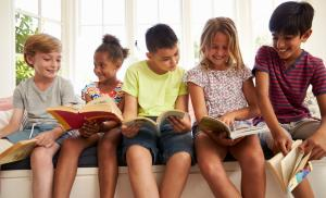 2019/09/group-of-multicultural-children-reading-on-window-seat-picture-id614860072.jpg