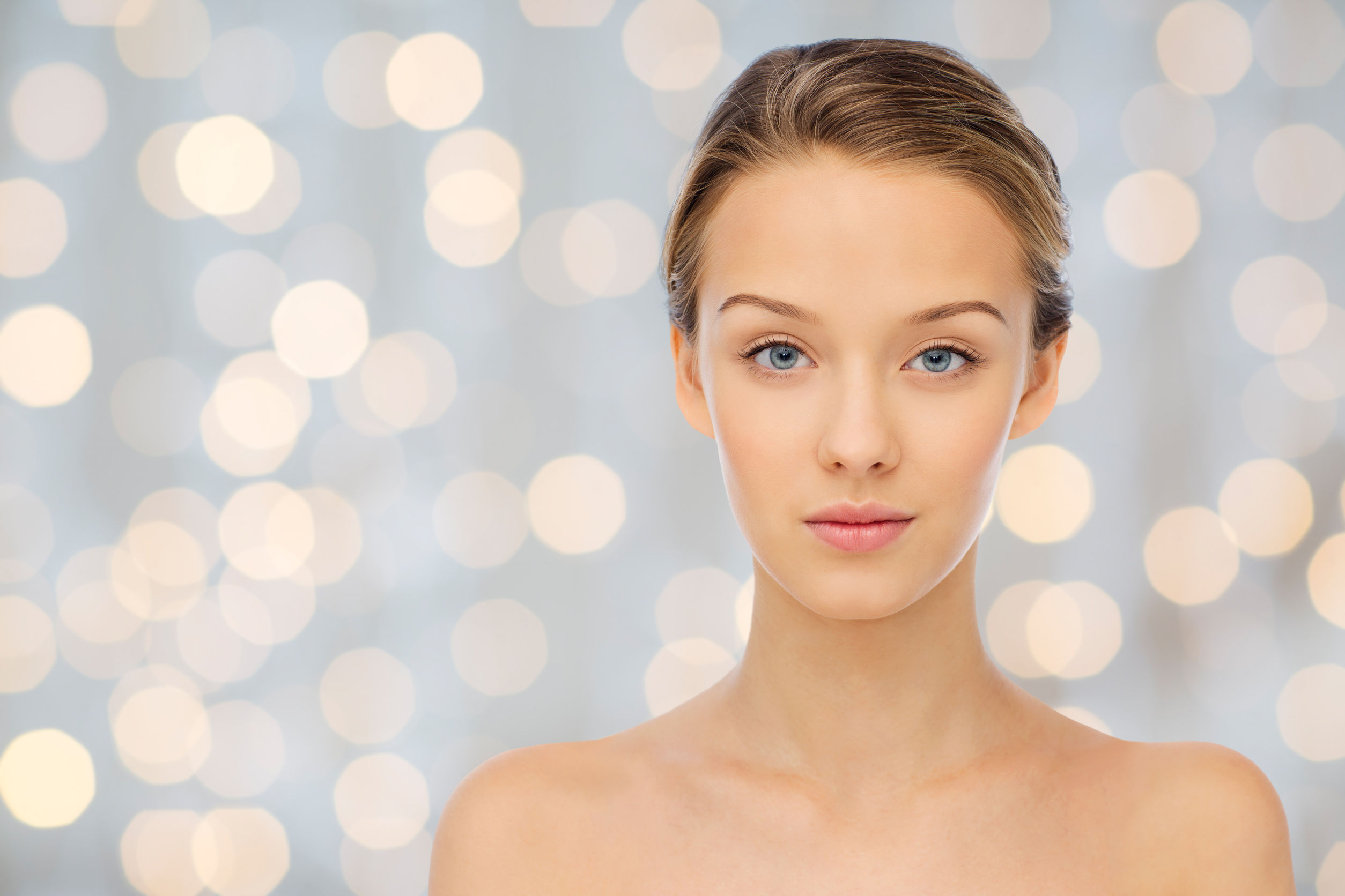 51385373 - beauty, people and health concept - young woman face and shoulders over holidays lights background