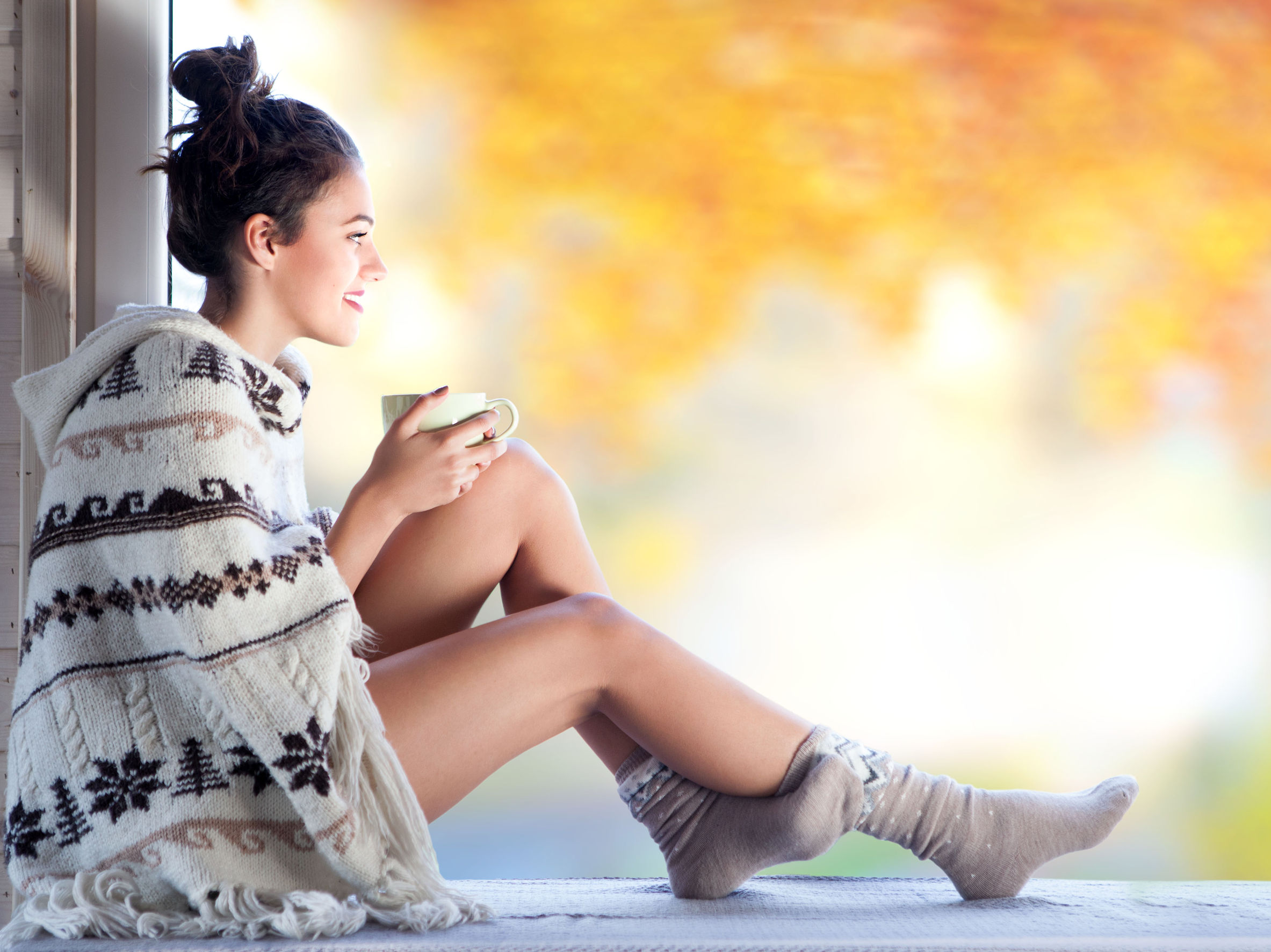 45215465 - young beautiful brunette woman with cup of coffee wearing knitted nordic print poncho sitting home by the window. blurred garden fall background.