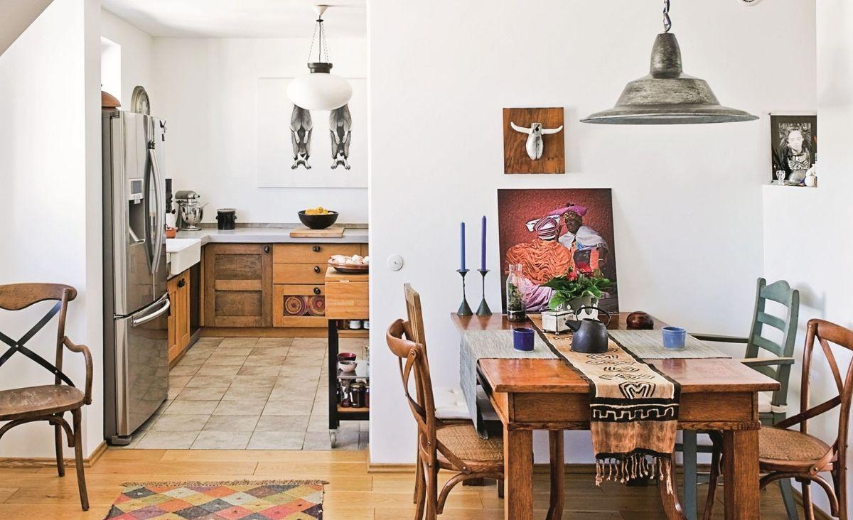 Stary drewniany stół, a nad nim dzieła przyjaciół: rzeźba Marka Bimera oraz fotografie Cezarego Filewa i Tomka Sikory (Fot. Jakub Pajewski)kuchnia