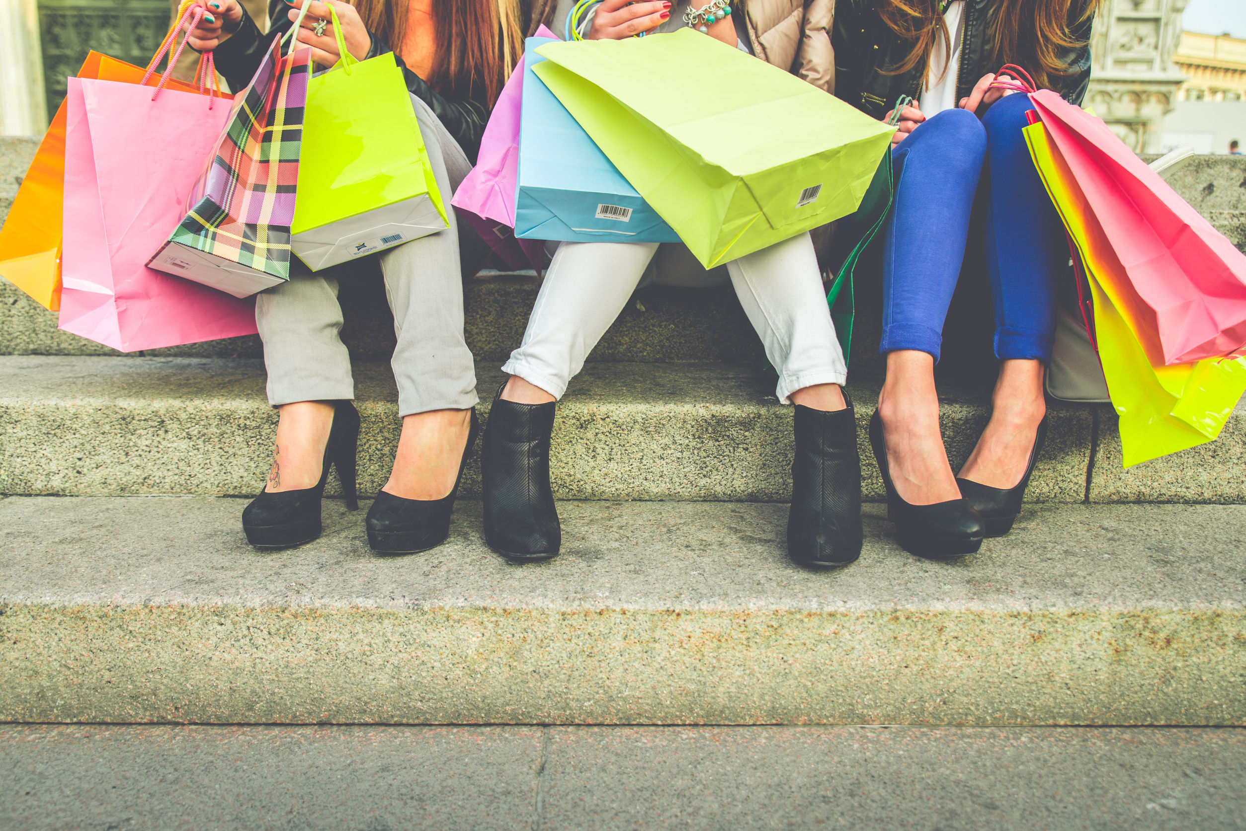 33400918 - women with high heels and shopping bags - three girls sitting on stairs and chatting after buying presents