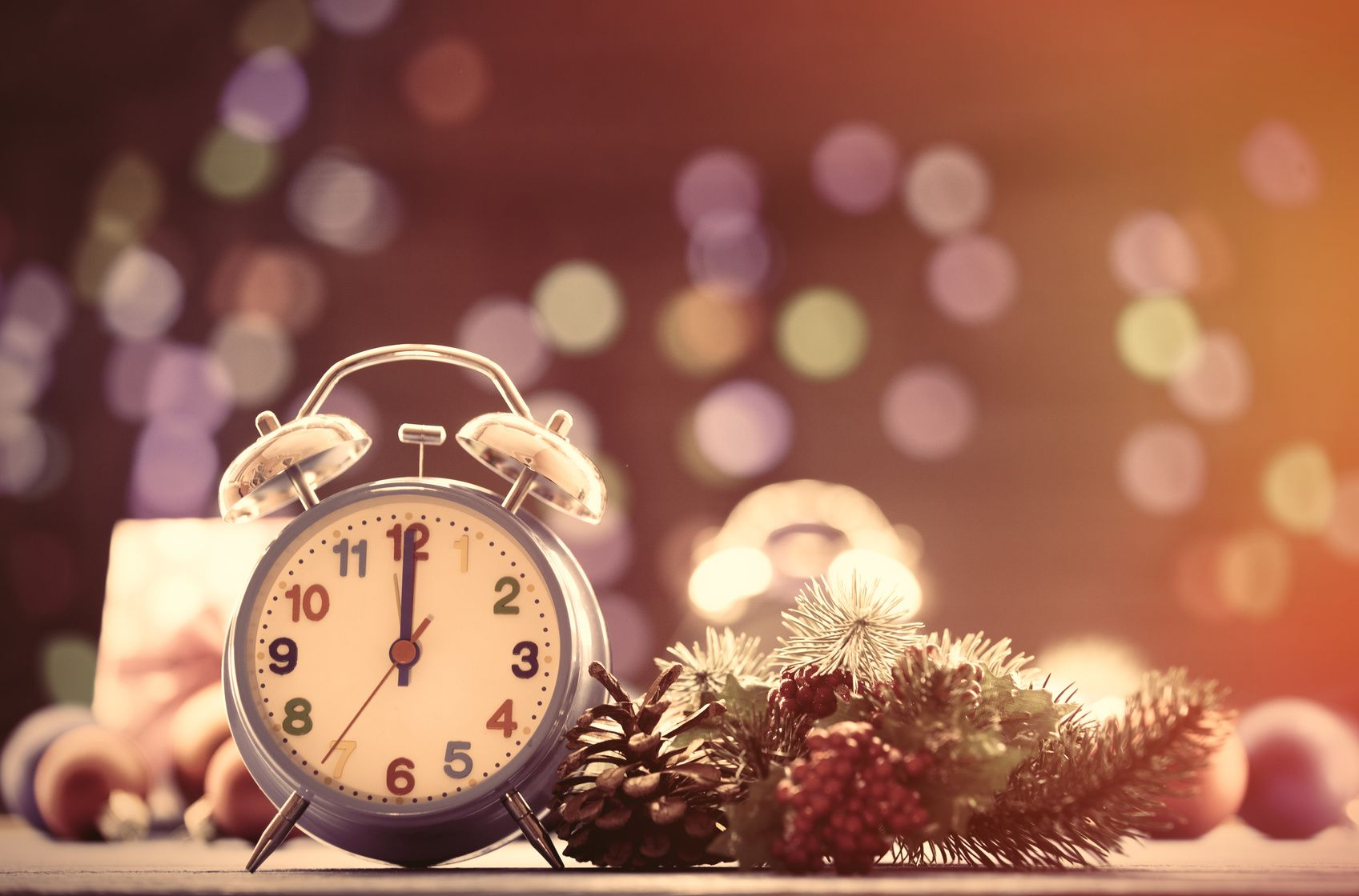 Clock and pine branch with Christmas lights on background
