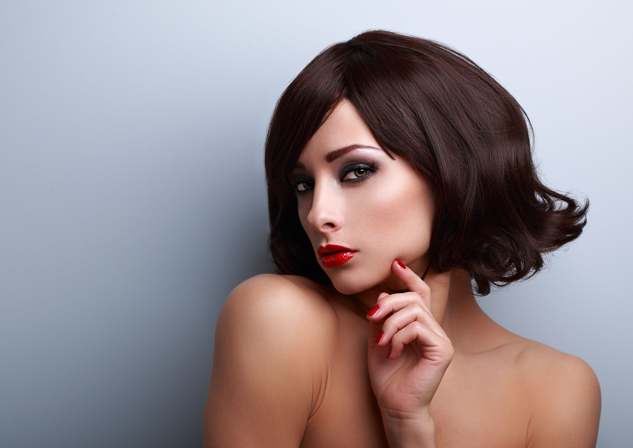 40094184 - beautiful makeup woman with short hairstyle and red nails gloss with empty copy space on blue background